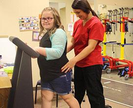 girl walking on treadmill with therapist