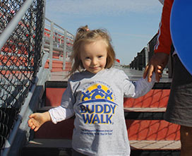 little girl walking down stairs with a buddy walk Tshirt on