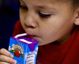 child drinking from juice box