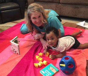 therapist playing with a child on a play mat