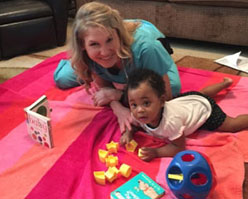Happy child working with therapist on a play mat