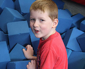 Boy plaing in foam cube pit